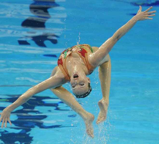 A member of the Ukraine's synchronised swimming team executes a move in the free combination final synchronised swimming competition in the FINA World Championships at the indoor stadium of the Oriental Sports Center, in Shanghai, on July 21, 2011. AFP PHOTO / MARK RALSTON