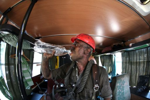 A rescuer drinks water as he rests at Sukhodolskaya-Vostochnaya coal mine  in Lugansk region on July 29, 2011. Eighteen miners died and another 20 were missing Friday after an explosion in the coal mine in eastern Ukraine known to be dangerous due to large methane build-ups, officials said. AFP PHOTO/ Alexander KHUDOTEPLY