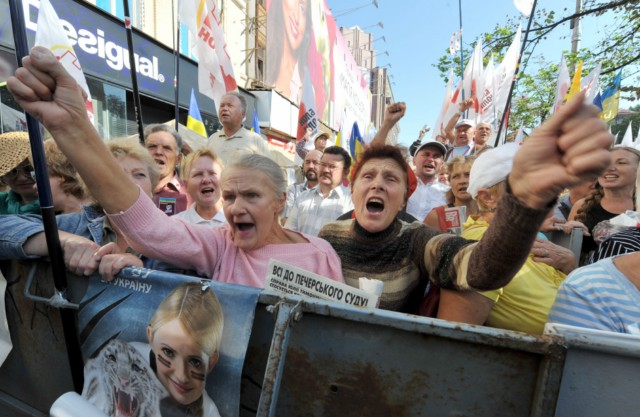 "Supporters of Ukraine's former prime minister Yulia Tymoshenko cheer and shout slogans in front of the Pechersk district court on August 8, 2011 in Kiev as Tymoshenko's return to trial today on charges of abuse of power over gas deals she signed with Russia in 2009. Tymoshenko was placed under arrest for contempt of court three days ago after describing her successor as ""corrupt"" and mocking the judge on Twitter.   AFP PHOTO / GENYA SAVILOV
