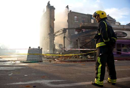 A fireman stands near a burnt-out pub on High Road in Tottenham, north London on August 7, 2011.  Two police cars and a large number of buildings were on Saturday set ablaze in north London following a protest over the fatal shooting of a 29-year-old man in an armed stand-off with officers.  The patrol cars were torched as dozens gathered outside the police station on the High Road in Tottenham.AFP PHOTO/LEON NEAL