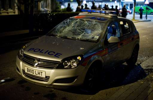 A police car shows severe damage caused by youths in Enfield, north London on 7 August 2011. Two police cars and a large number of buildings were on Saturday set ablaze in Tottenham, north London following a protest over the fatal shooting of a 29-year-old man in an armed stand-off with officers. The patrol cars were torched as dozens gathered outside the police station on the High Road in Tottenham.AFP PHOTO/LEON NEAL
