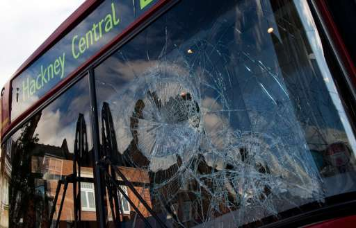 A damaged London bus is seen on a Mare Street in Hackney, north London on 8 August 2011.  Now in it's third night of unrest, London has seen sporadic outbreaks of looting and clashes both north and south of the river Thames. Two police cars and a large number of buildings were on Saturday set ablaze in Tottenham, north London following a protest over the fatal shooting of a 29-year-old man in an armed stand-off with officers.  The patrol cars were torched as dozens gathered outside the police station on the High Road in Tottenham. AFP PHOTO / LEON NEAL