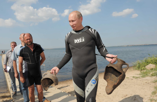 Russian Prime Minister Vladimir Putin holds two ancient amphorae he found while scuba diving in Taman Bay as he visits an underwater archaeological site at Phanagoria on the Taman Peninsula on August 10, 2011. Russia's hard man Prime Minister Vladimir Putin pulled on a wetsuit Wednesday and went scuba diving at an ancient Greek Black Sea site in the latest populist stunt ahead of next year's elections. AFP PHOTO / RIA NOVOSTI / POOL / ALEXEY DRUZHININ