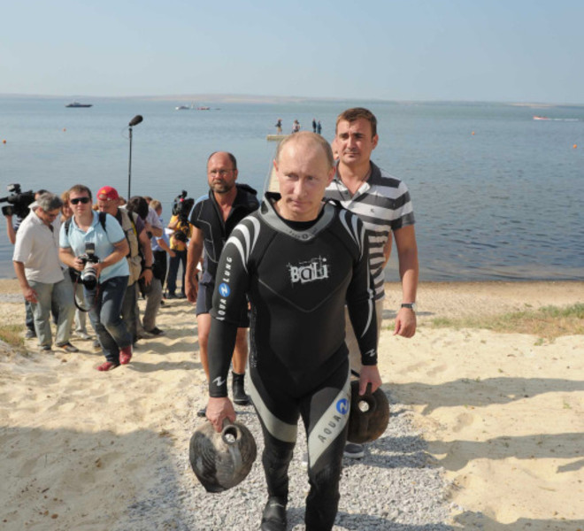 Russian Prime Minister Vladimir Putin carries two ancient amphorae he found while scuba diving in Taman Bay as he visits an underwater archaeological site at Phanagoria on the Taman Peninsula on August 10, 2011. Russia's hard man Prime Minister Vladimir Putin pulled on a wetsuit Wednesday and went scuba diving at an ancient Greek Black Sea site in the latest populist stunt ahead of next year's elections. AFP PHOTO / RIA NOVOSTI / POOL / ALEXEY DRUZHININ