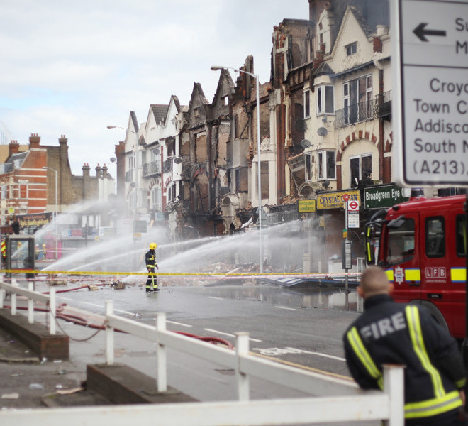 CROYDON, ENGLAND - AUGUST 09:  Fire officers damp down smouldering buildings on London Road on August 9, 2011 in Croydon, England. Emergency services have been cleaning up after a third night of rioting in and around London and other areas of England.  (Photo by Peter Macdiarmid/Getty Images)