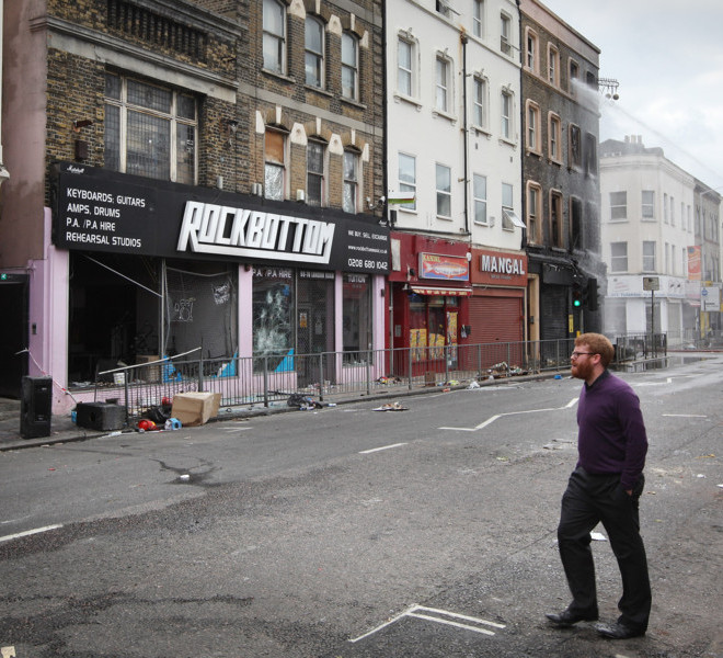 CROYDON, ENGLAND - AUGUST 09:  A man walks past burnt shops on London Road on August 9, 2011 in Croydon, England. Emergency services have been cleaning up after a third night of rioting in and around London and other areas of England.  (Photo by Peter Macdiarmid/Getty Images)