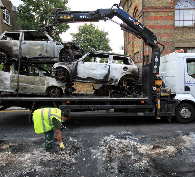LONDON, ENGLAND - AUGUST 09:  Burnt out cars are removed from a residential street in Hackney on August 9, 2011 in London, England. Emergency services have been cleaning up after a third night of rioting in and around London and other areas of England.  (Photo by Matt Cardy/Getty Images)