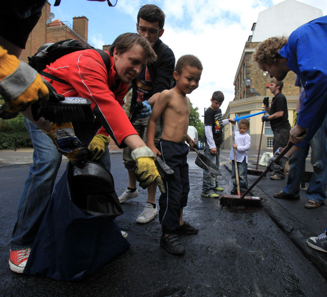 LONDON, ENGLAND - AUGUST 09:  Local residents start to clear up in Hackney on August 9, 2011 in London, England. Emergency services have been cleaning up after a third night of rioting in and around London and other areas of England.  (Photo by Matt Cardy/Getty Images)