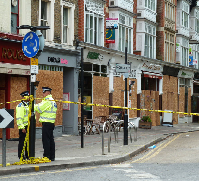 LONDON, ENGLAND - AUGUST 10:  Police stand guard in front of boarded up shops and businesses which were attacked in Ealing Green following Monday night's speight of rioting, on August 10, 2011 in London, England. After three nights of rioting and looting in and around London, the chaos has spread to other cities around Britain.   (Photo by Jim Dyson/Getty Images)