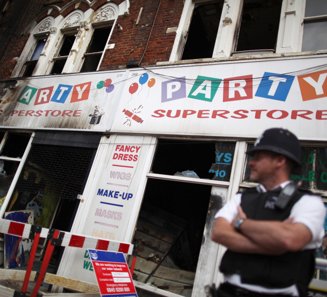 LONDON, ENGLAND - AUGUST 10:  A policeman stands outside a fire-damaged shop in Clapham Junction on August 10, 2011 in London, England. As trouble erupted through the night in other major cities across England, London remained mostly quiet after 16,000 police were deployed.  (Photo by Peter Macdiarmid/Getty Images)