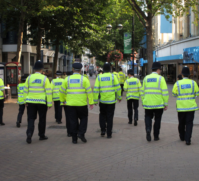 CROYDON, ENGLAND - AUGUST 09:  Police walk through the main shopping street on August 9, 2011 in Croydon, England. Thousands of extra police are on duty in the capital in an attempt to stop widespread looting and rioting for a fourth night.  Emergency services have been cleaning up after a third night of rioting in and around London and other areas of England.  (Photo by Peter Macdiarmid/Getty Images)