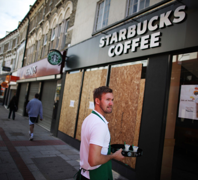 LONDON, ENGLAND - AUGUST 10: A member of staff at Starbucks stands outside the partly boarded up cafe to offer free drinks to passers-by in Clapham Junction on August 10, 2011 in London, England. As trouble erupted through the night in other major cities across England, London remained mostly quiet after 16,000 police were deployed.  (Photo by Peter Macdiarmid/Getty Images)