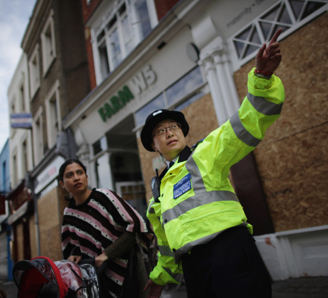 LONDON, ENGLAND - AUGUST 10:  A police officer offers directions to a member of the public after road closures in Ealing on August 10, 2011 in London, England. After three nights of rioting and looting in and around London, the chaos has spread to other cities around Britain.  (Photo by Dan Kitwood/Getty Images)