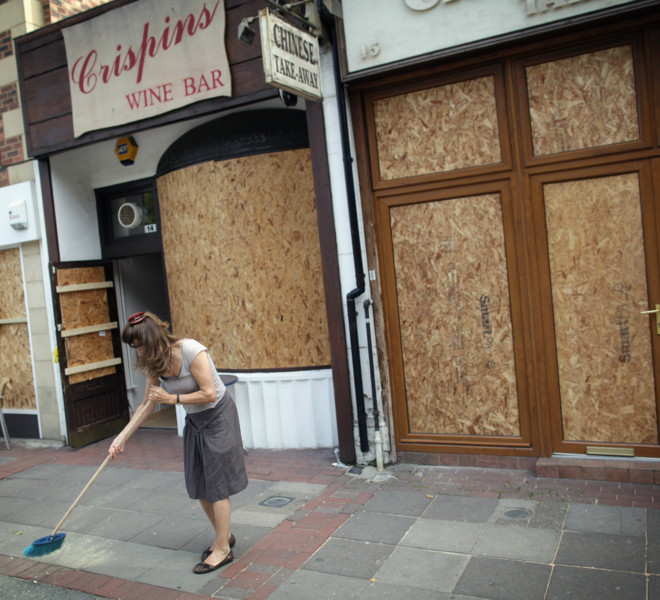 LONDON, ENGLAND - AUGUST 10:  A shop owner sweeps up outside her property in Ealing on August 10, 2011 in London, England. After three nights of rioting and looting in and around London, the chaos has spread to other cities around Britain.  (Photo by Dan Kitwood/Getty Images)