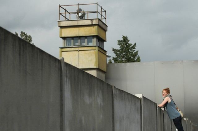 BERLIN, GERMANY - AUGUST 05:  A visitor standing on a ladder looks over a still-existing section of the Berlin Wall into the so-called 'death strip,' where East German border guards had the order to shoot anyone attempting to flee into West Berlin, as an original watchtower stands behind at the Bernauer Strasse memorial on August 5, 2011 in Berlin, Germany. The city of Berlin will mark the 50th anniversary of the construction of the Wall on August 13. The Berlin Wall was originally built in 1961 by the communist authorities of East Germany in order to stop East Germans from fleeing west, and up to an estimated 245 people died trying to do so until the Wall came down in 1989.   (Photo by Sean Gallup/Getty Images)