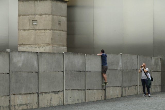 BERLIN, GERMANY - AUGUST 05:  A visitor standing on a ladder looks over a still-existing section of the Berlin Wall into the so-called 'death strip,' where East German border guards had the order to shoot anyone attempting to flee into West Berlin, as an original watchtower stands behind at the Bernauer Strasse memorial on August 5, 2011 in Berlin, Germany. The city of Berlin will mark the 50th anniversary of the construction of the Wall on August 13. The Berlin Wall was originally built in 1961 by the communist authorities of East Germany in order to stop East Germans from fleeing west, and up to an estimated 245 people died trying to do so until the Wall came down in 1989.   (Photo by Sean Gallup/Getty Images), BERLIN, GERMANY - AUGUST 10:  A costumed border guard stands in front of a poster near a still-existing section of the Berlin Wall, the so called East Side Gallery, where East German border guards once had the order to shoot anyone attempting to flee into West Berlin on August 10, 2011 in Berlin, Germany. The city of Berlin will mark the 50th anniversary of the construction of the Wall on August 13. The Berlin Wall was originally built in 1961 by the communist authorities of East Germany in order to stop East Germans from fleeing west, and up to an estimated 245 people died trying to do so until the Wall came down in 1989.  (Photo by Andreas Rentz/Getty Images), BERLIN, GERMANY - AUGUST 10:  Visitors watch through a metal door at a still-existing section of the Berlin Wall, where East German border guards once had the order to shoot anyone attempting to flee into West Berlin on August 10, 2011 in Berlin, Germany. The city of Berlin will mark the 50th anniversary of the construction of the Wall on August 13. The Berlin Wall was originally built in 1961 by the communist authorities of East Germany in order to stop East Germans from fleeing west, and up to an estimated 245 people died trying to do so until the Wall came down in 1989.  (Photo by Andreas Rentz/Getty Images), BERLIN, GERMANY - AUGUST 10:  Visitors ride past a still-existing section of the Berlin Wall, where East German border guards once had the order to shoot anyone attempting to flee into West Berlin on August 10, 2011 in Berlin, Germany. The city of Berlin will mark the 50th anniversary of the construction of the Wall on August 13. The Berlin Wall was originally built in 1961 by the communist authorities of East Germany in order to stop East Germans from fleeing west, and up to an estimated 245 people died trying to do so until the Wall came down in 1989.  (Photo by Andreas Rentz/Getty Images), BERLIN, GERMANY - AUGUST 10:  A still-existing section of the Berlin Wall, where East German border guards once had the order to shoot anyone attempting to flee into West Berlin is pictured on August 10, 2011 in Berlin, Germany. The city of Berlin will mark the 50th anniversary of the construction of the Wall on August 13. The Berlin Wall was originally built in 1961 by the communist authorities of East Germany in order to stop East Germans from fleeing west, and up to an estimated 245 people died trying to do so until the Wall came down in 1989.  (Photo by Andreas Rentz/Getty Images), BERLIN, GERMANY - AUGUST 05:  A guide instructs visitors at a still-existing section of the Berlin Wall, where East German border guards once had the order to shoot anyone attempting to flee into West Berlin, as an original watchtower stands behind at the Bernauer Strasse memorial on August 5, 2011 in Berlin, Germany. The city of Berlin will mark the 50th anniversary of the construction of the Wall on August 13. The Berlin Wall was originally built in 1961 by the communist authorities of East Germany in order to stop East Germans from fleeing west, and up to an estimated 245 people died trying to do so until the Wall came down in 1989.  (Photo by Sean Gallup/Getty Images), BERLIN, GERMANY - AUGUST 05:  A visitor looks over a still-existing section of the Berlin Wall into the so-called 'death strip,' where East German border guards once had the order to shoot anyone attempting to flee into West Berlin at the Bernauer Strasse memorial on August 5, 2011 in Berlin, Germany. The city of Berlin will mark the 50th anniversary of the construction of the Wall on August 13. The Berlin Wall was originally built in 1961 by the communist authorities of East Germany in order to stop East Germans from fleeing west, and up to an estimated 245 people died trying to do so until the Wall came down in 1989.  (Photo by Sean Gallup/Getty Images)