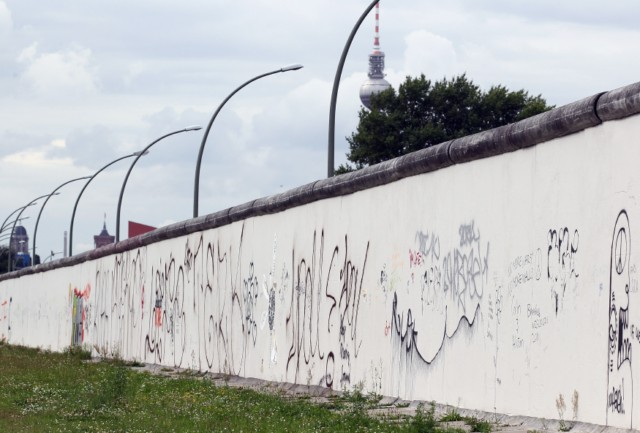 BERLIN, GERMANY - AUGUST 05:  A visitor standing on a ladder looks over a still-existing section of the Berlin Wall into the so-called 'death strip,' where East German border guards had the order to shoot anyone attempting to flee into West Berlin, as an original watchtower stands behind at the Bernauer Strasse memorial on August 5, 2011 in Berlin, Germany. The city of Berlin will mark the 50th anniversary of the construction of the Wall on August 13. The Berlin Wall was originally built in 1961 by the communist authorities of East Germany in order to stop East Germans from fleeing west, and up to an estimated 245 people died trying to do so until the Wall came down in 1989.   (Photo by Sean Gallup/Getty Images), BERLIN, GERMANY - AUGUST 10:  A costumed border guard stands in front of a poster near a still-existing section of the Berlin Wall, the so called East Side Gallery, where East German border guards once had the order to shoot anyone attempting to flee into West Berlin on August 10, 2011 in Berlin, Germany. The city of Berlin will mark the 50th anniversary of the construction of the Wall on August 13. The Berlin Wall was originally built in 1961 by the communist authorities of East Germany in order to stop East Germans from fleeing west, and up to an estimated 245 people died trying to do so until the Wall came down in 1989.  (Photo by Andreas Rentz/Getty Images), BERLIN, GERMANY - AUGUST 10:  Visitors watch through a metal door at a still-existing section of the Berlin Wall, where East German border guards once had the order to shoot anyone attempting to flee into West Berlin on August 10, 2011 in Berlin, Germany. The city of Berlin will mark the 50th anniversary of the construction of the Wall on August 13. The Berlin Wall was originally built in 1961 by the communist authorities of East Germany in order to stop East Germans from fleeing west, and up to an estimated 245 people died trying to do so until the Wall came down in 1989.  (Photo by Andreas Rentz/Getty Images), BERLIN, GERMANY - AUGUST 10:  Visitors ride past a still-existing section of the Berlin Wall, where East German border guards once had the order to shoot anyone attempting to flee into West Berlin on August 10, 2011 in Berlin, Germany. The city of Berlin will mark the 50th anniversary of the construction of the Wall on August 13. The Berlin Wall was originally built in 1961 by the communist authorities of East Germany in order to stop East Germans from fleeing west, and up to an estimated 245 people died trying to do so until the Wall came down in 1989.  (Photo by Andreas Rentz/Getty Images), BERLIN, GERMANY - AUGUST 10:  A still-existing section of the Berlin Wall, where East German border guards once had the order to shoot anyone attempting to flee into West Berlin is pictured on August 10, 2011 in Berlin, Germany. The city of Berlin will mark the 50th anniversary of the construction of the Wall on August 13. The Berlin Wall was originally built in 1961 by the communist authorities of East Germany in order to stop East Germans from fleeing west, and up to an estimated 245 people died trying to do so until the Wall came down in 1989.  (Photo by Andreas Rentz/Getty Images)