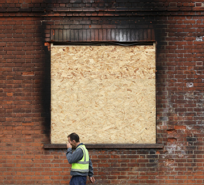 TOTTENHAM, ENGLAND - AUGUST 16:  A man walks past a boarded up building in Tottenham following the riots in the area last week on August 16, 2011 in London, England. The Home Secretary Theresa May has today announced that new guidelines will be issued to police forces to grant them tougher measures to deal with future public order issues.  (Photo by Oli Scarff/Getty Images)