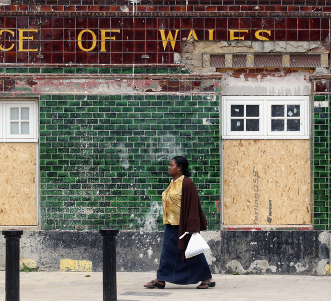 TOTTENHAM, ENGLAND - AUGUST 16:  A woman walks past the boarded up Prince of Wales pub in Tottenham following the riots in the area last week on August 16, 2011 in London, England. The Home Secretary Theresa May has today announced that new guidelines will be issued to police forces to grant them tougher measures to deal with future public order issues.  (Photo by Oli Scarff/Getty Images)