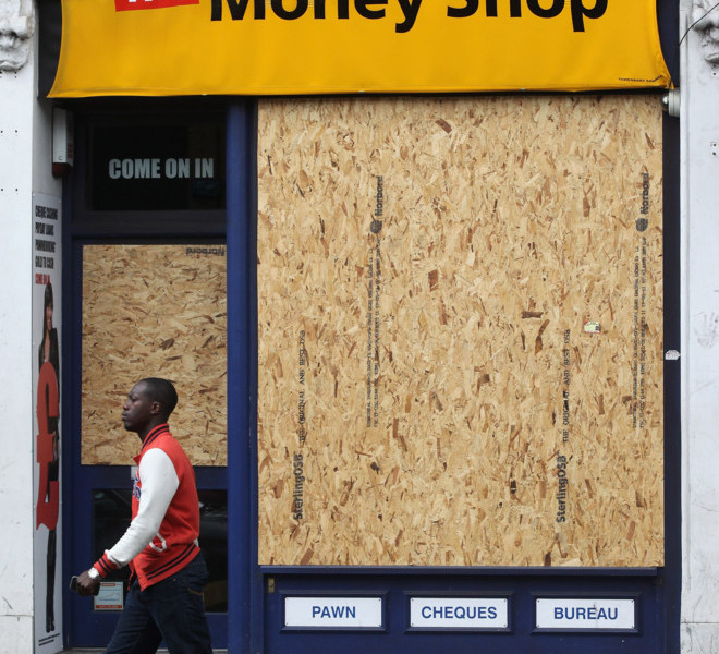 TOTTENHAM, ENGLAND - AUGUST 16:  A man walks past a boarded up shopin Tottenham following the riots in the area last week on August 16, 2011 in London, England. The Home Secretary Theresa May has today announced that new guidelines will be issued to police forces to grant them tougher measures to deal with future public order issues.  (Photo by Oli Scarff/Getty Images)