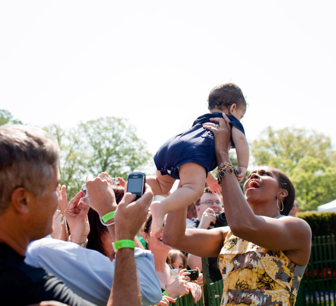 First Lady Michelle Obama lifts a baby while greeting the crowd at the annual Easter Egg Roll on the South Lawn of the White House, April 25, 2011. (Official White House Photo by Samantha Appleton)