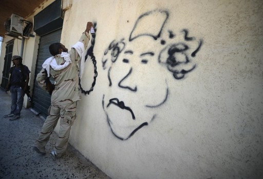 A rebel sprays graffiti depicting Col. Moamer Kadhafi on a wall in Gadayem, west of the capital Tripoli, on August 21, 2011. Explosions and gunfire rocked Tripoli as a months-long uprising pushed through the gates of the Libyan capital, with rebels insisting they are close to toppling Moamer Kadhafi.   AFP PHOTO/FILIPPO MONTEFORTE