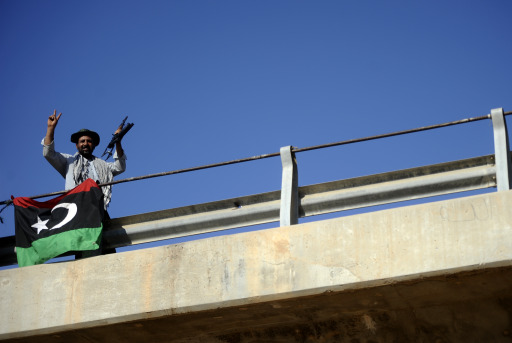 A Libyan rebel flashes the V-sign from the captured 27th Bridge, several kilometers west of the centre of Tripoli, on August 21, 2011, as the rebels said victory in Tripoli was imminent and urged NATO to join the final battle with Apache assault helicopters against fighters loyal to Libyan leader Moamer Kadhafi.  AFP PHOTO / FILIPPO MONTEFORTE