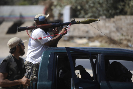 A rebel shoulders an RPG in Gadayem, west of the capital Tripoli, on August 21, 2011. Explosions and gunfire rocked Tripoli as a months-long uprising pushed through the gates of the Libyan capital, with rebels insisting they are close to toppling Moamer Kadhafi.   AFP PHOTO/FILIPPO MONTEFORTE