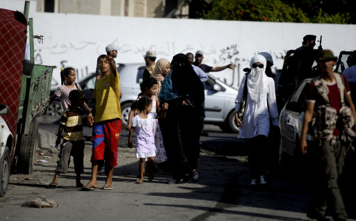 Women, children and rebel fighters gather on a street in the Libyan capital Tripoli, on August 22, 2011, as heavy fighting raged near the Tripoli compound of embattled Libyan leader Moamer Kadhafi, while jubilant rebel forces surged into the symbolic heart of the capital.  AFP PHOTO / FILIPPO MONTEFORTE