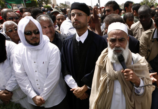 (FILES)--A May 2, 2011 file photo shows Mohammed (L) and Saif al-Islam Kadhafi (2nd L), sons of embattled Libyan leader Moamer Kadhafi, attend the funeral of their brother Seif al-Arab at the Al-Hani cemetery in Tripoli after the 29-year-old was killed along with three of the leader's grandchildren in a NATO airstrike early on May 1.  Libyan rebels were in the heart of Tripoli on August 22, 2011, after surging into the capital in a final drive to oust Moamer Kadhafi, seizing swathes of the city and arresting the strongman's son, Seif al-Islam. AFP PHOTO/MAHMUD TURKIA