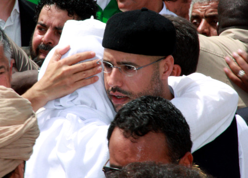 (FILES)--A May 2, 2011 file photo shows Mohammed (L) and Saif al-Islam Kadhafi (R), sons of embattled Libyan leader Moamer Kadhafi, embrace during the funeral of their brother Seif al-Arab at the Al-Hani cemetery in Tripoli after the 29-year-old was killed along with three of the leader's grandchildren in a NATO airstrike early on May 1.  Libyan rebels were in the heart of Tripoli on August 22, 2011, after surging into the capital in a final drive to oust Moamer Kadhafi, seizing swathes of the city and arresting the strongman's son, Seif al-Islam.  AFP PHOTO/STR