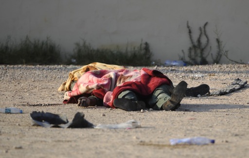 A dead fighter is covered with a blanket as he lies on a street in the Libyan capital Tripoli, on August 22, 2011, a day after heavy fighting raged near the Tripoli compound of embattled Libyan leader Moamer Kadhafi, as jubilant rebel forces surged into the symbolic heart of the capital.  AFP PHOTO / FILIPPO MONTEFORTE