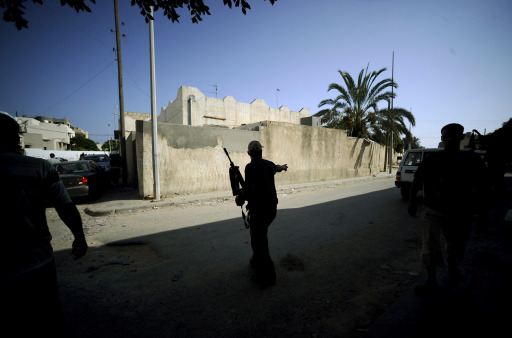 Rebel fighters walk along a residential street in the Libyan capital Tripoli, on August 22, 2011, as heavy fighting raged near the Tripoli compound of embattled Libyan leader Moamer Kadhafi, while jubilant rebel forces surged into the symbolic heart of the capital.  AFP PHOTO / FILIPPO MONTEFORTE