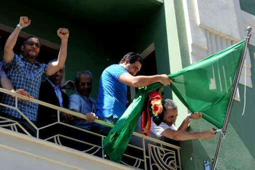 Libyan consul Abdulmacit Ali Said (R) removes the Kadhafi regime's Libyan flag with demonstrators on a balcony of the Libyan consulate in Istanbul on August 22, 2011 as Libyan rebels entered the heart of Tripoli in a final drive to oust Kadhafi. The group of some 40 people came to the consulate and Abdulmecit Ali Said allowed some 10 of them in, to remove the green flag and flew Libya's National Transitional Council's flag instead.   AFP PHOTO