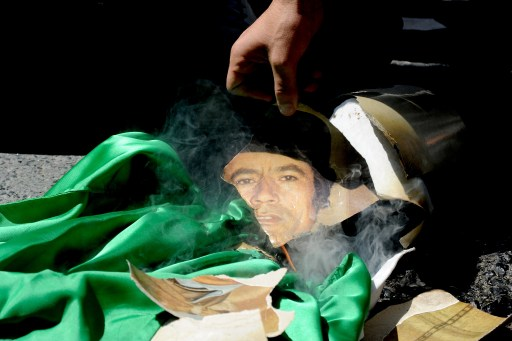 Libyan opposition demonstrators set fire to a portrait of Libya's leader Moamer Kadhafi and his regime's green flag outside the Libyan consulate in Istanbul on August 22, 2011 as Libyan rebels entered the heart of Tripoli in a final drive to oust Kadhafi. A group of some 40 people came to the consulate and Abdulmecit Ali Said, the Libyan consul allowed some 10 of them in, to change the flag. Opposition groups were also shown staging a protest at the Libyan embassy in Ankara, tearing down the pictures of Kadhafi.  AFP PHOTO