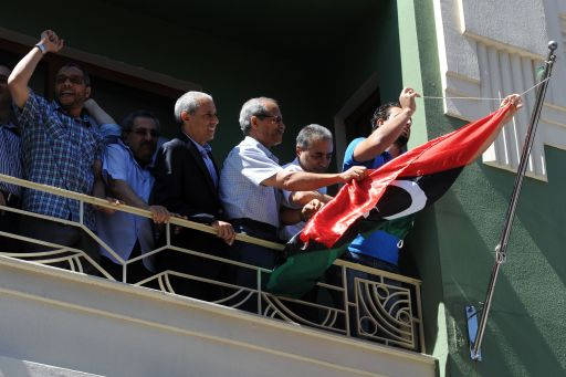Libyan opposition demonstrators instal Libya's National Transitional Council's flag on a balcony of the Libyan consulate in Istanbul on August 22, 2011 as Libyan rebels entered the heart of Tripoli in a final drive to oust Kadhafi. The group of some 40 people came to the consulate and Abdulmecit Ali Said (2nd R), the Libyan consul, allowed some 10 of them in, to remove the green flag of the Moamer Kadhafi regime and flew the Council's flag instead.   AFP PHOTO
