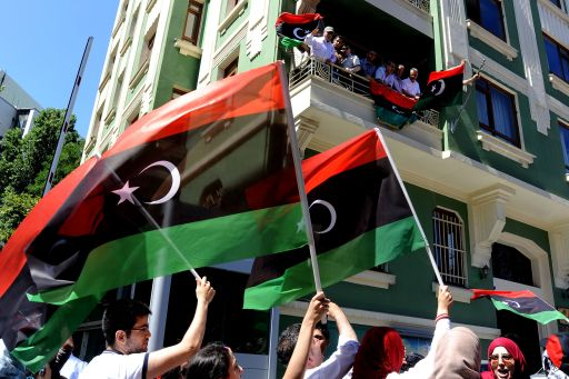 Libyan opposition demonstrators wave Libya's National Transitional Council flags outside the Libyan consulate in Istanbul on August 22, 2011 as Libyan rebels entered the heart of Tripoli in a final drive to oust Kadhafi. A group of some 40 people came to the consulate and Abdulmecit Ali Said, the Libyan consul allowed some 10 of them in, to remove Kadhafi's regime flag and flew the council's flag instead. Opposition groups were also shown staging a protest at the Libyan embassy in Ankara, tearing down the pictures of Kadhafi.     AFP PHOTO