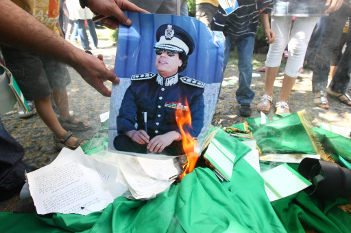 Demonstrators set fire to a poster of Libyan leader Moamer Kadhafi, copies of his Green Book and Libyan flags during a protest against Kadhafi outside the Libyan embassy in Ankara on August 22, 2011. Libyan opposition groups hauled down the flag of the Moamer Kadhafi regime at the embassy in the Turkish capital and flew the rebel flag, as fighting rages in Libya today near the compound of embattled of the Libyan leader  and in other parts of Tripoli, a day after jubilant rebels overran the symbolic heart of the capital. AFP PHOTO/ADEM ALTAN