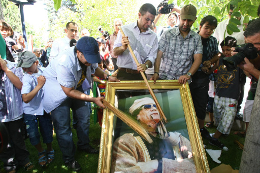 Demonstrators smash a portrait of Moamer Kadhafi during a protest against Kadhafi outside the Libyan embassy in Ankara on August 22, 2011. Libyan opposition groups hauled down the flag of the Moamer Kadhafi regime at the embassy in the Turkish capital and flew the rebel flag, as fighting rages in Libya today near the compound of embattled of the Libyan leader  and in other parts of Tripoli, a day after jubilant rebels overran the symbolic heart of the capital. AFP PHOTO/ADEM ALTAN