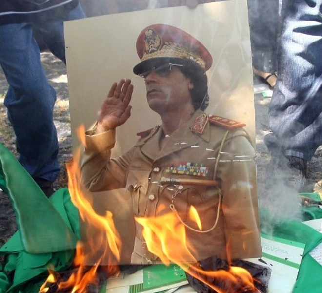 A portrait of Libyan leader Moamer Kadhafi and copies of his green book are set on fire by demonstrators during a protest outside the Libyan embassy in Ankara on August 22, 2011 as Libyan rebels entered the heart of Tripoli in a final drive to oust Kadhafi. Libyan opposition groups hauled down the flag of Kadhafi's regime at the embassy and flew the rebel flag instead. The new flag belongs to Libya's National Transitional Council, which was recognized in July by Turkey as the legitimate representative of the Libyan people.    AFP PHOTO / ADEM ALTAN