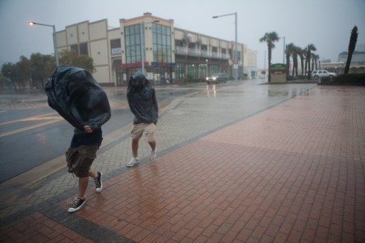 VIRGINIA BEACH, VA - AUGUST 27: Two men wear garbage bags to shield themselves from Hurricane Irene's heavy rain on August 27, 2011 in Virginia Beach, Virginia. The Category 1 storm made landfall in North Carolina early this morning.   Brendan Hoffman/Getty Images/AFP== FOR NEWSPAPERS, INTERNET, TELCOS & TELEVISION USE ONLY ==