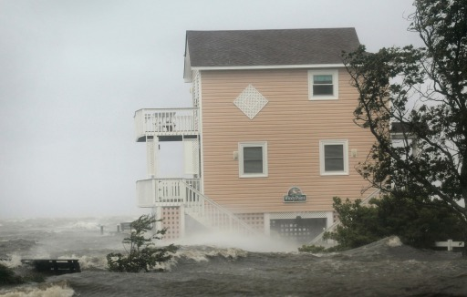 KILL DEVIL HILLS, NC - AUGUST 27: Floodwater surrounds a home as storm surge from Hurricane Irene begins to make its way on shore on August 27, 2011 in Kill Devil Hills, North Carolina. Hurricane Irene hit Dare County, which sits along the Outer Banks and includes the vacation towns of Nags Head, Kitty Hawk and Kill Devil Hills, as a category one hurricane around mid-day today causing wind damage and flooding.   Scott Olson/Getty Images/AFP== FOR NEWSPAPERS, INTERNET, TELCOS & TELEVISION USE ONLY ==