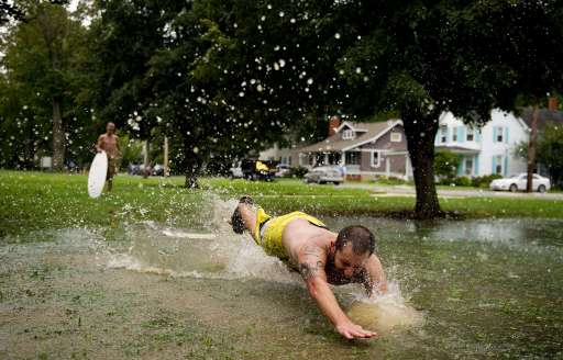 Mark Wade (R) trips into a puddle while surfing with his friend Craig Busick (L) in a large puddle in front of the Board of Education in Centreville, MD, August 28, 2011, after Hurricane Irene.                       AFP PHOTO/Jim WATSON