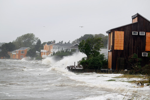 HAMPTON BAYS, NY - AUGUST 28: Waves are seen crashing around homes as Hurricane Irene arrives on August 28, 2011 in Hampton Bays, New York. While Hurricane Irene has now been downgraded to a tropical storm, it has knocked out power to more than 3 million people and is attributed to 11 deaths as it travels up the Eastern seaboard.   Joe Raedle/Getty Images/AFP== FOR NEWSPAPERS, INTERNET, TELCOS & TELEVISION USE ONLY ==