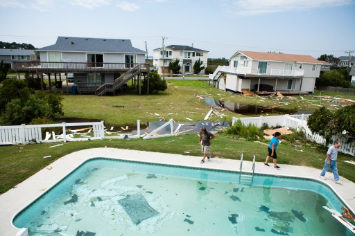 VIRGINIA BEACH, VA - AUGUST 28: Shane Argabright (L), a general contractor, surveys damage to a house belonging to Aileen Black (C) and Reed Black on Sandfiddler Rd. in Sandbridge the day after a tornado spawned by Hurricane Irene passed through on August 28, 2011 in Virginia Beach, Virginia. The Category 1 storm, which made landfall in North Carolina early yesterday morning, has been downgraded to a tropical storm, but knocked out power to more than 3 million people and is attributed to 15 deaths as it travels up the Eastern seaboard.   Brendan Hoffman/Getty Images/AFP== FOR NEWSPAPERS, INTERNET, TELCOS & TELEVISION USE ONLY ==