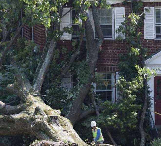 "A worker from Ex-Cel Tree Experts clears a tree fallen across the top of a house after Hurricane Irene in Washington, Sunday, August 28, 2011.  US President Barack Obama said Sunday, August 28, 2011, the Hurricane Irene recovery effort could go on for days or weeks, but hailed the disaster response operation as an ""exemplary"" display of good government.  The president, who took pains to show Americans he was in charge of the emergency effort, amid memories of the botched response to Hurricane Katrina in 2005, also remembered the 14 people killed in the storm.  AFP PHOTO / TOBY JORRIN"