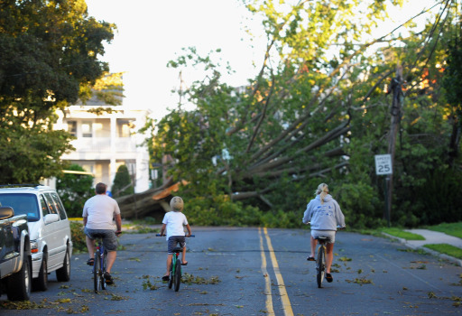 MANASQUAN, NJ - AUGUST 28: A family crosses police lines and rides towards a tree brought down by winds caused by Hurricane Irene on August 28, 2011 in Manasquan, New Jersey. While Hurricane Irene has now been downgraded to a tropical storm, it has knocked out power to more than 4.5 million people and is attributed to 19 deaths as it travels up the Eastern seaboard.   Michael Loccisano/Getty Images/AFP== FOR NEWSPAPERS, INTERNET, TELCOS & TELEVISION USE ONLY ==