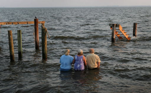 "NAGS HEAD, NC - AUGUST 28: Billy Stinson (R), his wife Sandra Stinson (C) and daughter Erin Stinson walk out to watch the sunset from the steps where their cottage once stood August 28, 2011 in Nags Head, North Carolina. The cottage, built in 1903 and destroyed yesterday by Hurrican Irene, was one of the first vacation cottages built on Albemarle Sound in Nags Head. Stinson has owned the home, which is listed in the National Register of Historic Places, since 1963. ""We were pretending, just for a moment, that the cottage was still behind us and we were just sitting there watching the sunset,"" said Erin afterward.   Scott Olson/Getty Images/AFP== FOR NEWSPAPERS, INTERNET, TELCOS & TELEVISION USE ONLY =="
