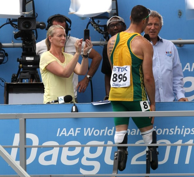 South Africa's Oscar Pistorius stands talking with a journalist at the end of his race in the men's 400 metres heats at the International Association of Athletics Federations (IAAF) World Championships in Daegu on August 28, 2011.        AFP PHOTO / ADRIAN DENNIS