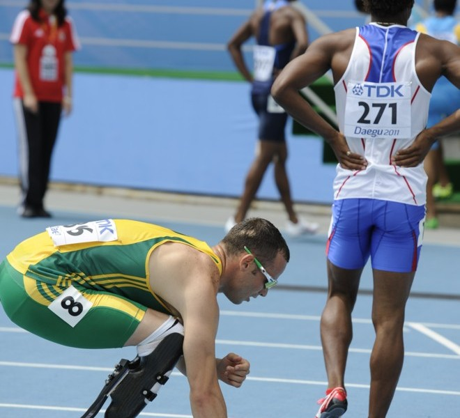 South Africa's Oscar Pistorius (L) crouches on the track at the end of his race in the men's 400 metres heats at the International Association of Athletics Federations (IAAF) World Championships in Daegu on August 28, 2011.       AFP PHOTO / PETER PARKS